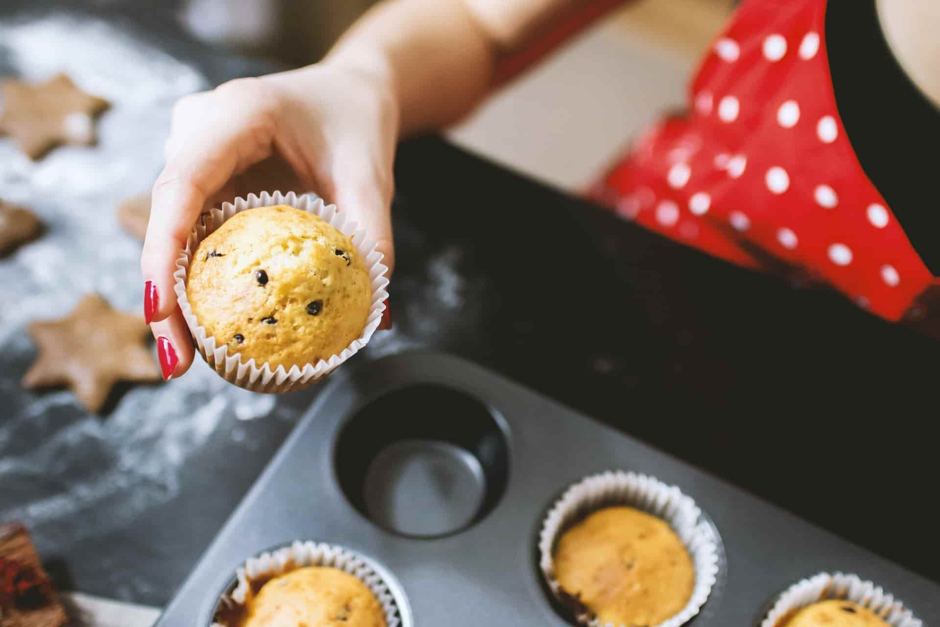 A person holding a muffin over in their hand with a muffin tray placed beneath
