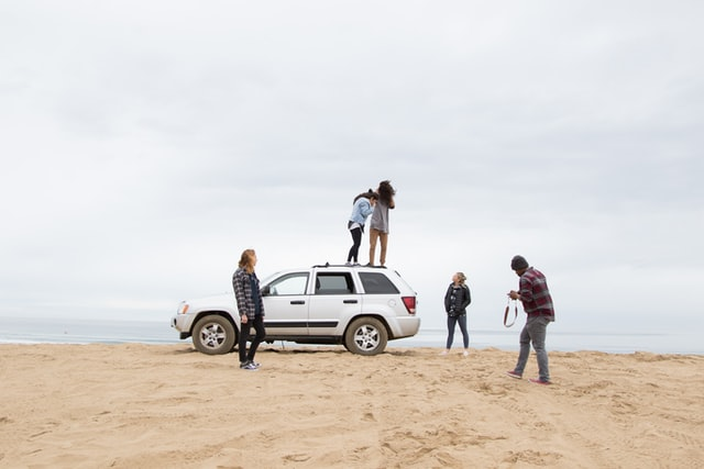 Quirky hen do ideas; a group of people standing near their 4x4 on a beach
