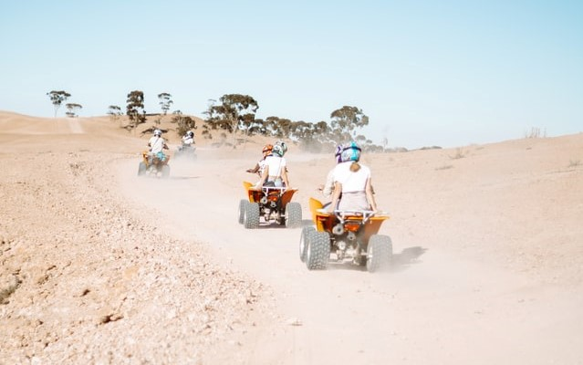 Quirky hen do ideas; people riding ATVs on an open muddy field