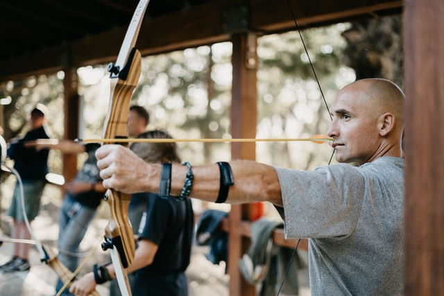 Common Archery Issues; man holding a bow and focusing on his shot