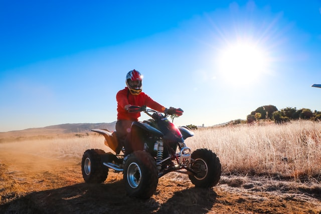 types of ATVs; a person riding a quad bike on an open field