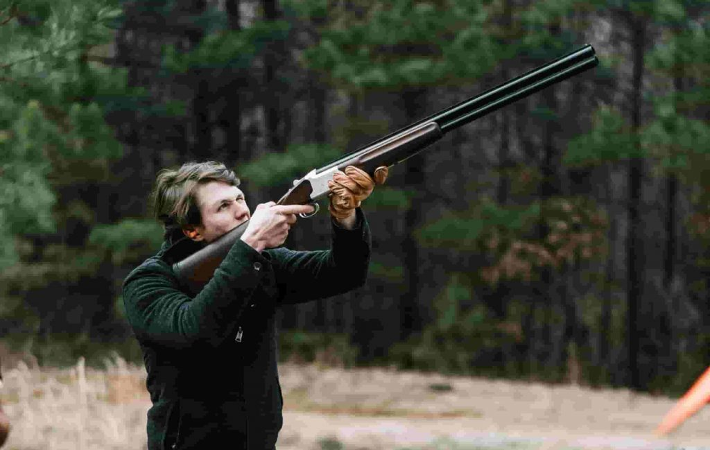 clay pigeon shooting safety tips; A man aiming to shoot mid air with a rifle