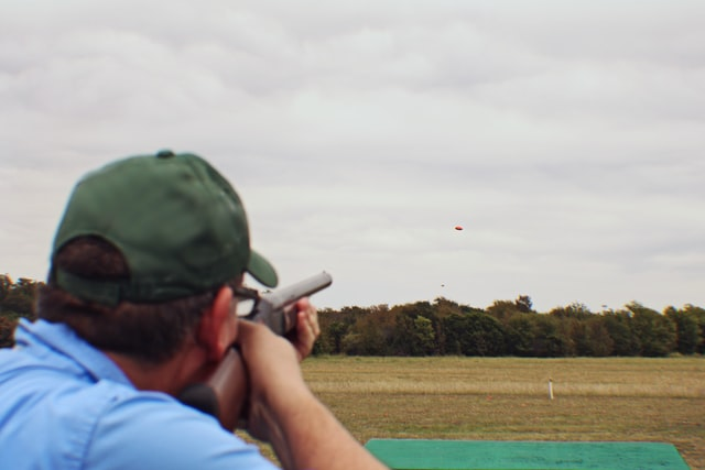 Back shot of a person aiming at a clay pigeon that is mid-air