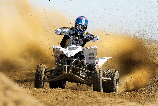 types of ATVs; a person riding a quad bike on a sandy trail, throwing sand on both sides