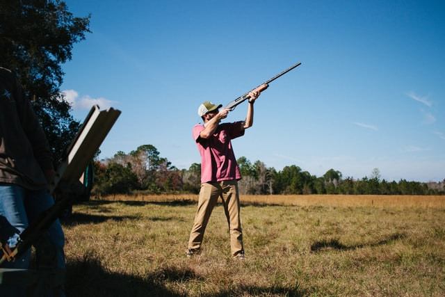 Clay Pigeon Shooting Mistakes; a person aiming their rifle in the air