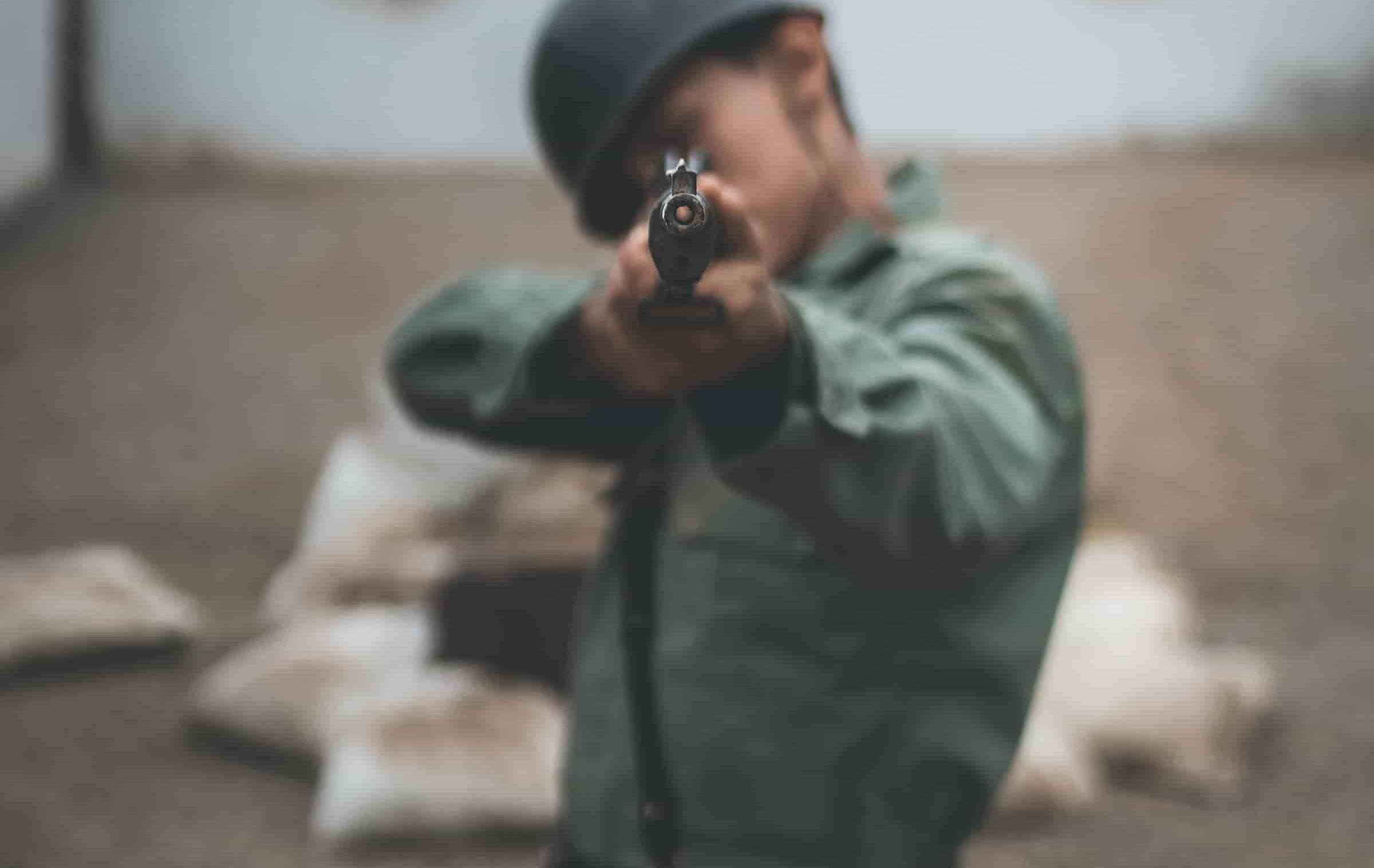 A man directly pointing his gun at the camera.