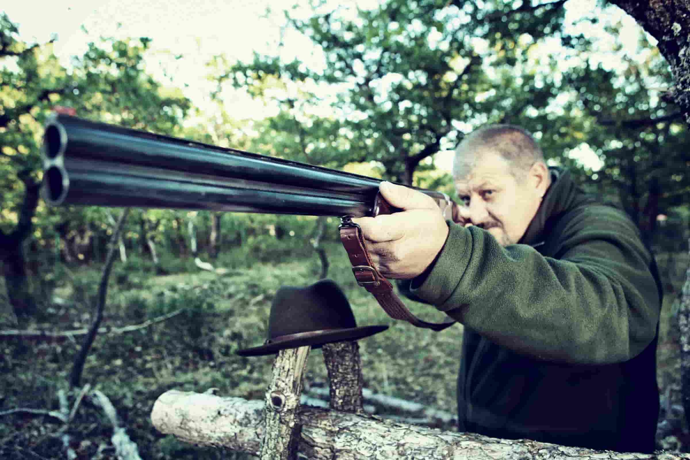 Clay pigeon shooting safety tips; A man ready to shoot with his head resting on a tree branch.