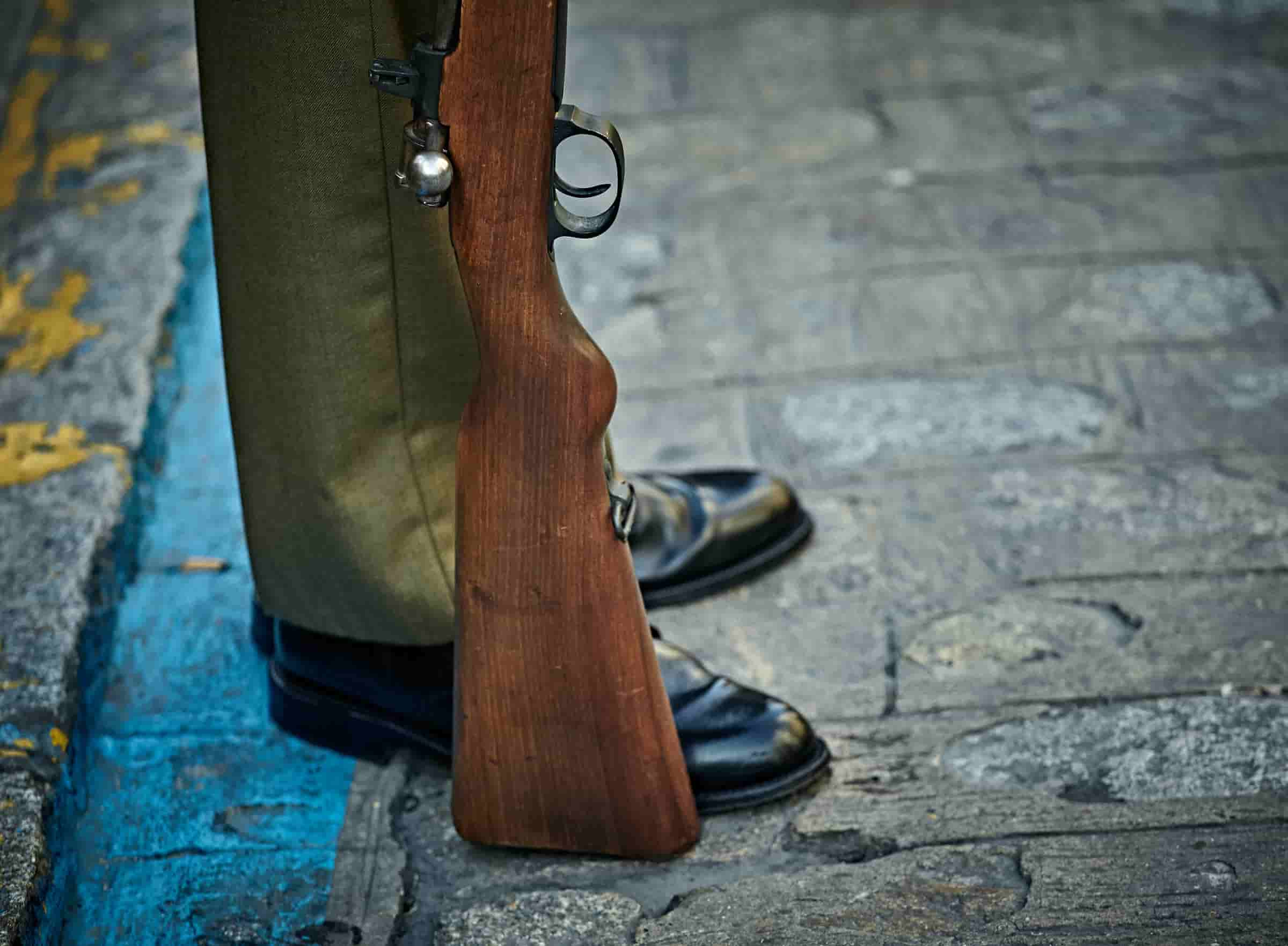 A person standing in formal shoes with the end of the gun resting on the ground.