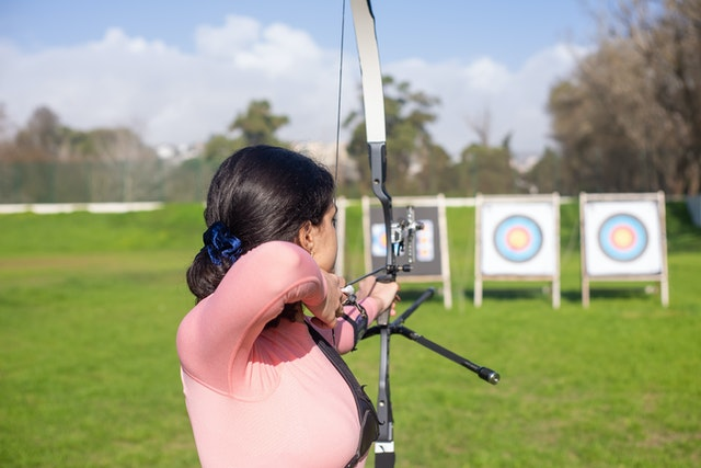 girl taking her aim whilst holding a modern bow