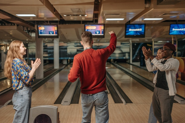 Company Outing; a group of people indulging in a game of bowling