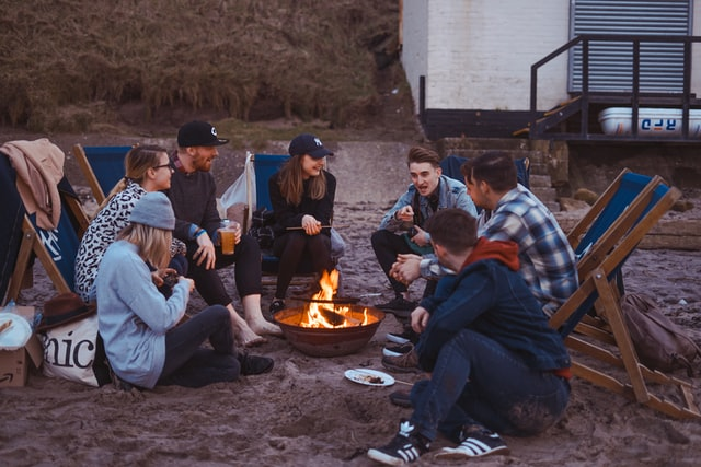 Unconventional Team Building Activities; A group of colleagues talking and sitting around a bonfire.