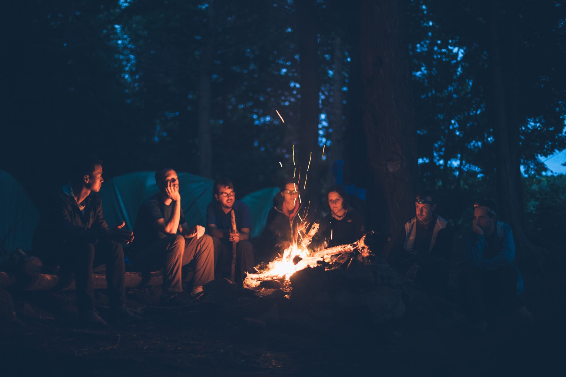 Team Building Activities; People sitting around a bonfire; connecting and talking.