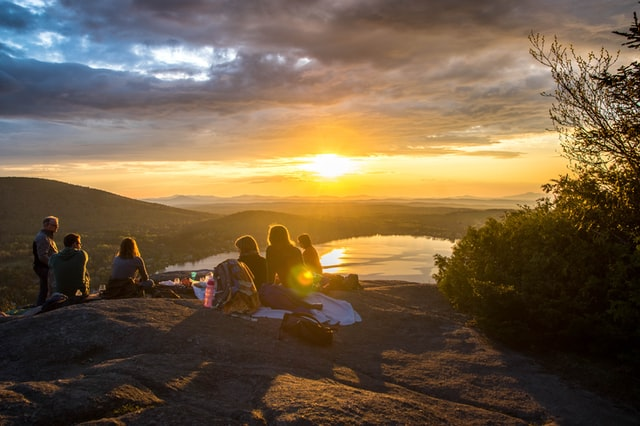 Company Outing; group of people sitting atop a mountain watching the sunset