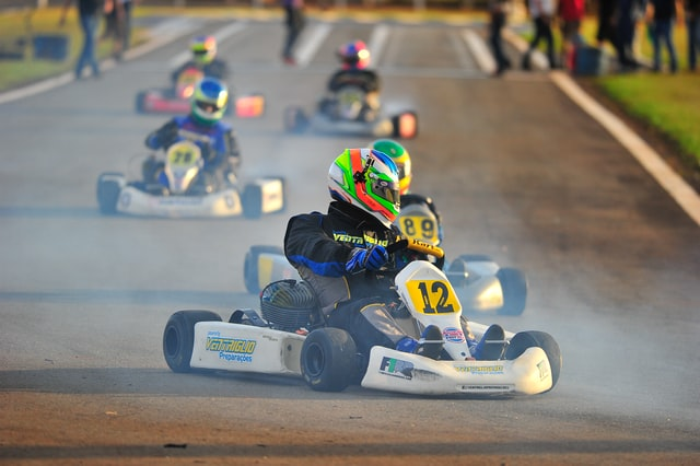 Company Outing; person driving a go-kart with other competitors in the background
