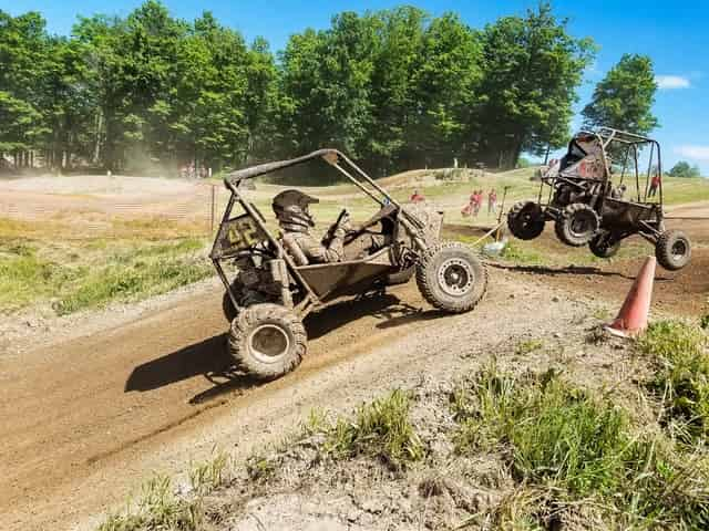Importance of team building activities; two people riding a buggy on a muddy terrain