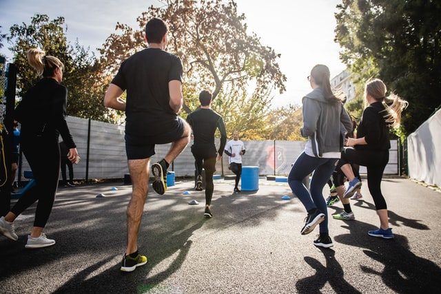 Indoor Vs Outdoor Team Building Activities; A fitness session of people being held outdoors