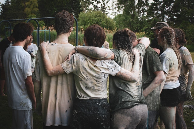 Indoor Vs Outdoor Team Building Activities; A group of people in muddy clothes after playing an outdoor activity.